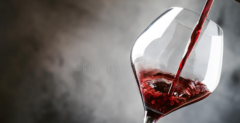 French dry red wine, pours into glass, gray background, banner, selective focus. French dry red wine, pours into glass, gray background, banner, selective  focus royalty free stock photography