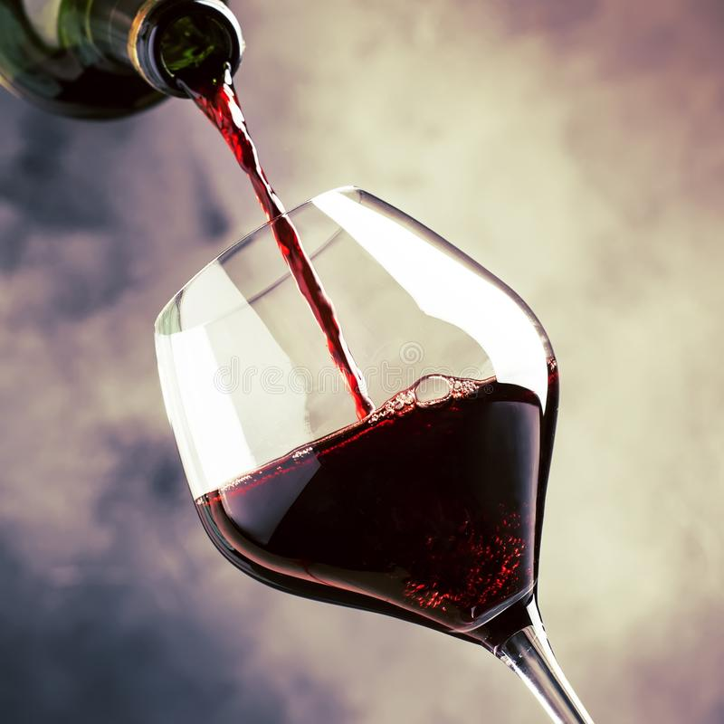 French dry red wine, pours into glass, gray background, selective focus. French dry red wine, pours into glass, gray background, selective  focus stock image