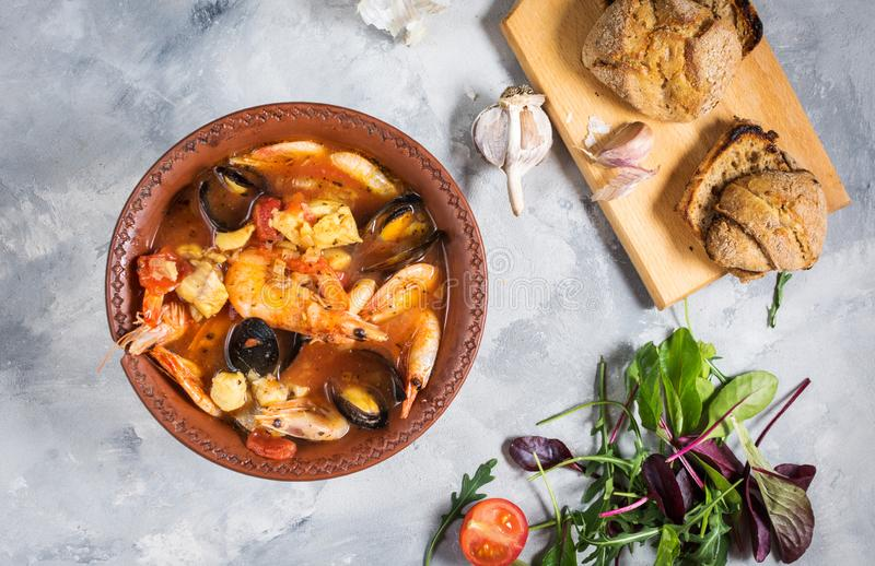 French fish soup Bouillabaisse with seafood, salmon fillet, shrimp, mussels on concrete background. Delicious dinner stock photography