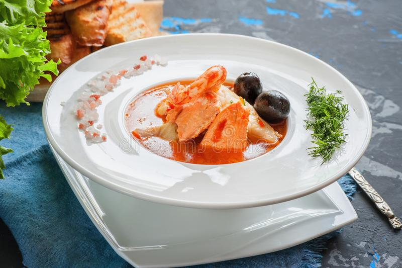 French fish soup Bouillabaisse with seafood, salmon fillet, shrimp, rich flavor, delicious dinner in a white beautiful royalty free stock images