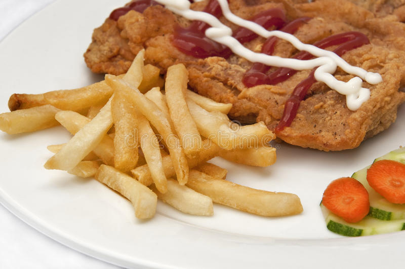 French fries. Chicken steak and french fries on the white plate stock photography