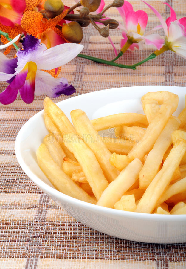 French fries. Plate of french fries on mat background with flowers stock images