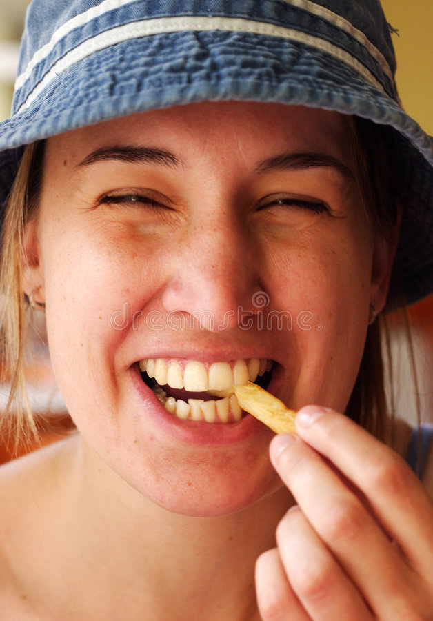French fries. Young woman laugh and eating french fries stock photography