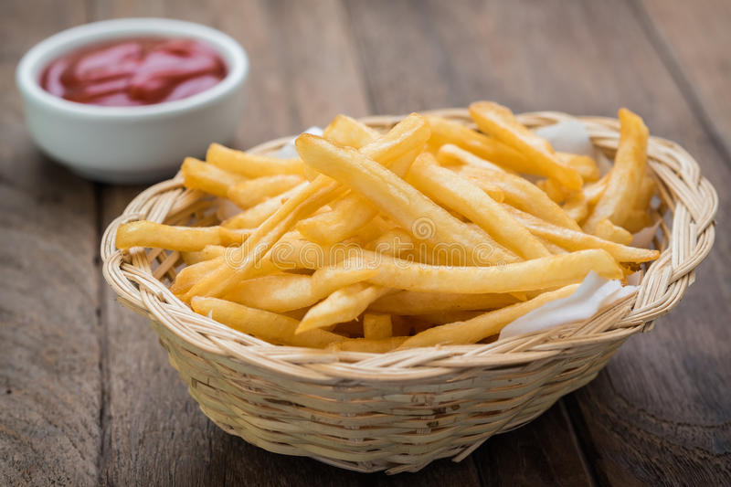 French fries in basket and ketchup on wooden table royalty free stock image