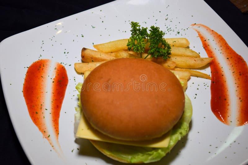 French fries, fresh tasty burger isolated on Black background royalty free stock images
