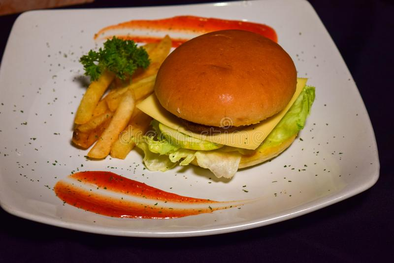 French fries, fresh tasty burger isolated on Black background royalty free stock photography