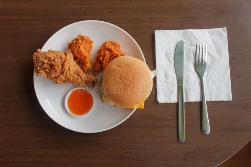 French fries and fried chicken are placed in a white plate on the table select focus, Close-up fast food stock photo