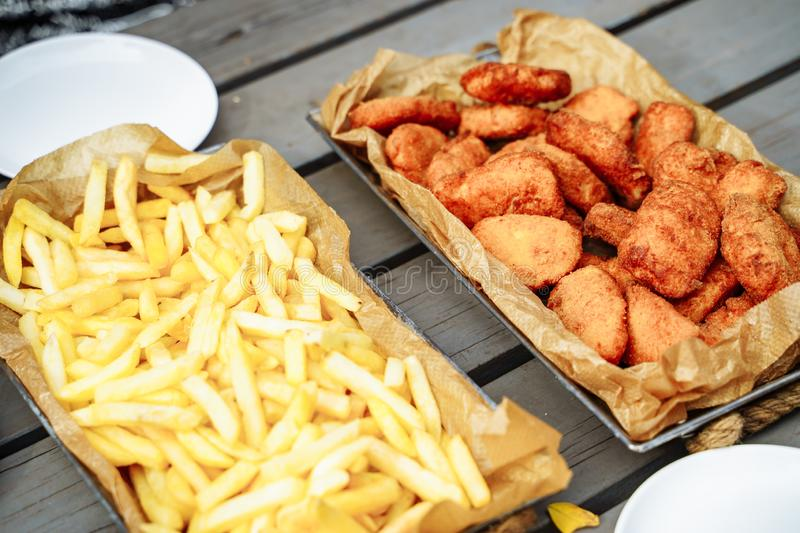 French fries and fried crispy chicken nuggets on wooden table stock images