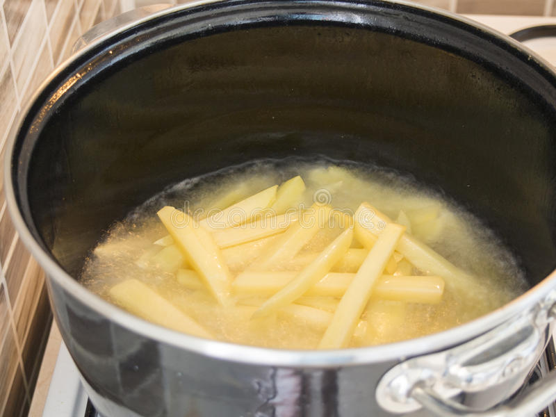 French fries in frying pan stock images