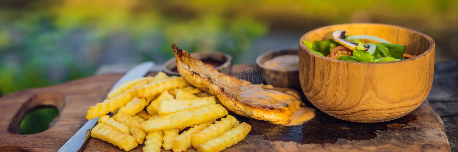 French fries, green salad with champignons and chicken breast. Lifestyle food BANNER, LONG FORMAT royalty free stock photo
