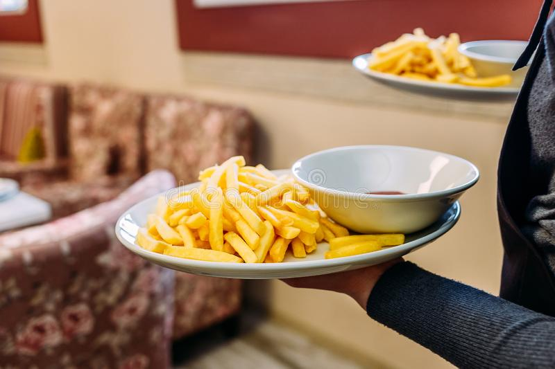 French fries in the hands of the waiter stock image