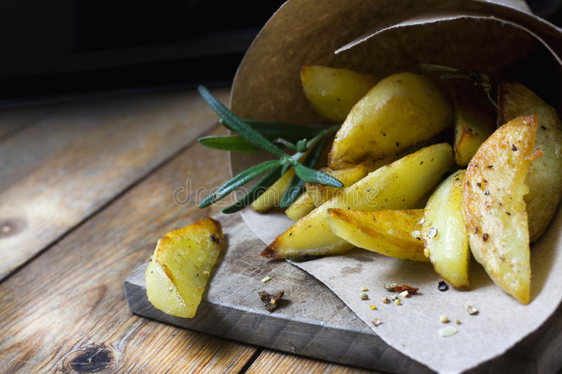 French fries with herbs and spices in recycled craft paper bag royalty free stock photography