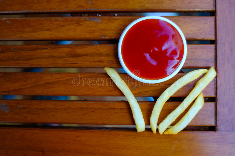 French fries. With ketchup on wooden background royalty free stock image