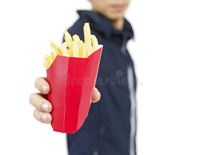 French fries. Man offering a pack of french fries stock photos