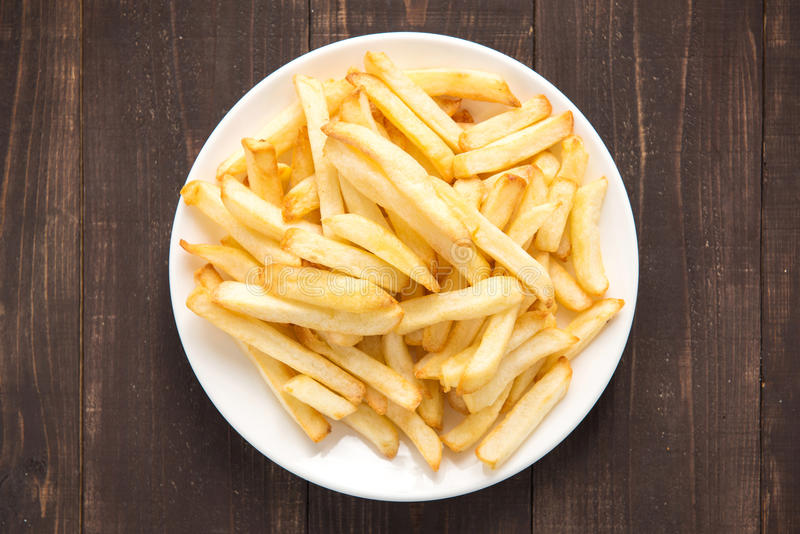 French fries on white dish on wooden background stock photo
