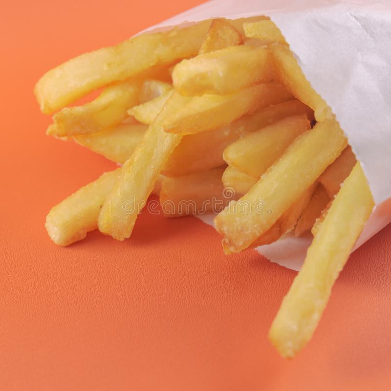 French fries in white paper bag on orange background. fast food royalty free stock photos
