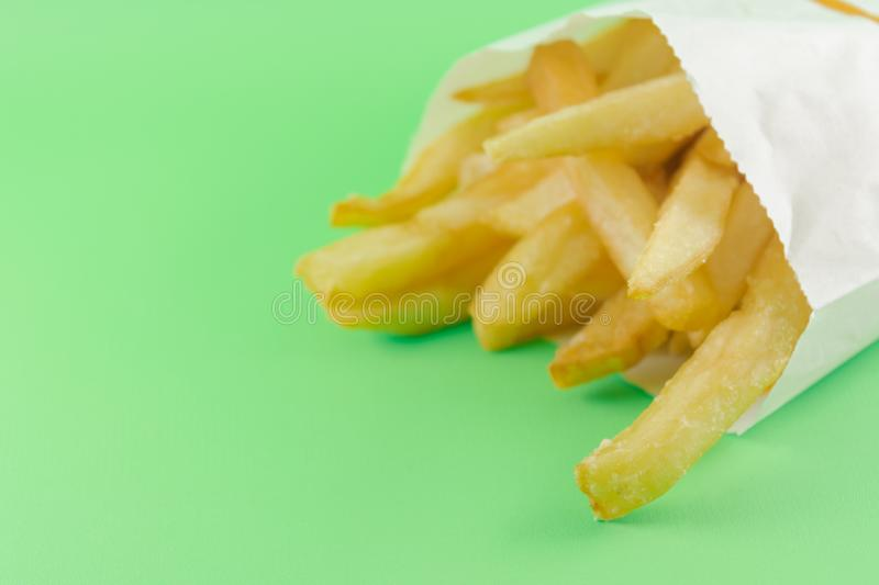 French fries in white paper bag on soft green background. fast food stock images