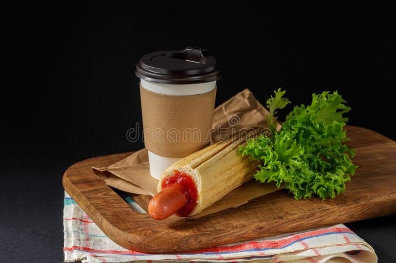 French Hot Dog and coffee on black background stock photos