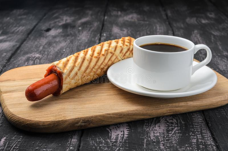 French Hot Dog and coffee on wooden table stock images