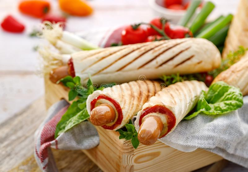 French Hot dogs with ketchup and mustard, delicious street food. In a wooden box royalty free stock photography