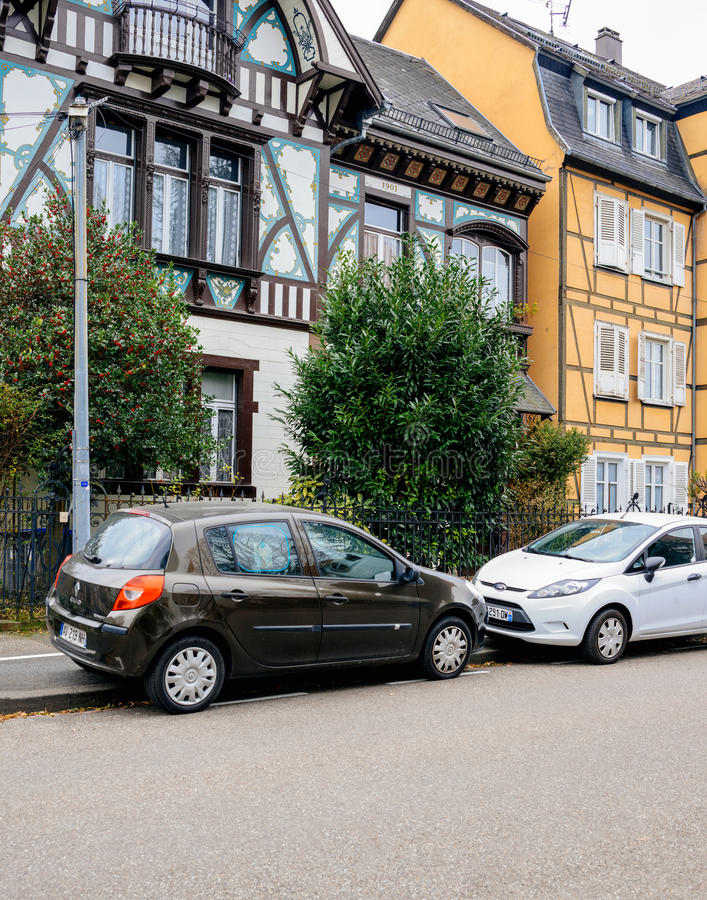 French house in Alsace with two parked cars in front. STRASBOURG, FRANCE - DEC 2, 2016: Renault Clio and Ford Fiesta in front of beautiful timbered house in stock photos