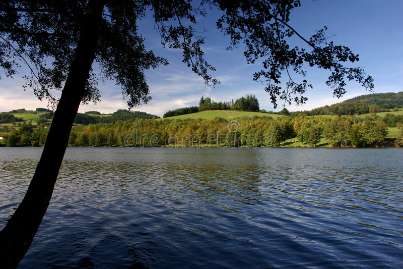 French Lake (lac des sapins). Black shadow of a tree, near deep blue waters of a mountain Lake in french country of Beaujolais stock photography