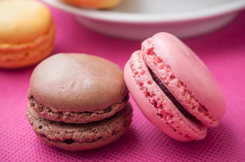 French macarons pastry and cup of coffeee. Assortment of french macarons pastry and cup of coffeee on pink background stock images