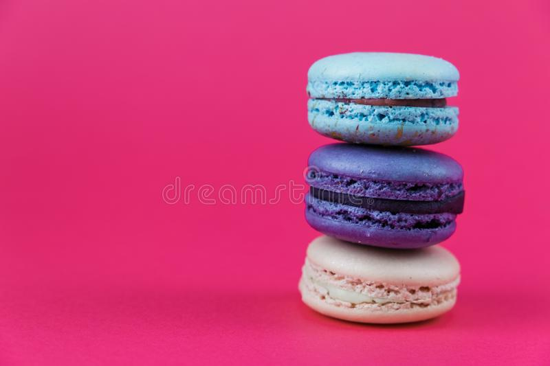 French macarons. Sweet colorful bisquits. Front view. Copy text space. Hot pink background. stock photo