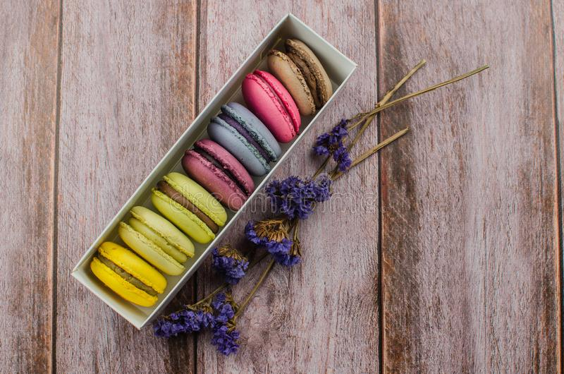 French macaroon cake. Macaroons in box with dried flowers on wood background stock photography