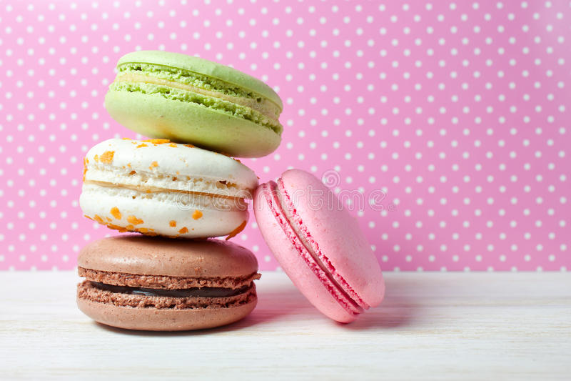 French macaroons .Dessert. Traditional French dessert makarons on a colorful polka dots background royalty free stock photos