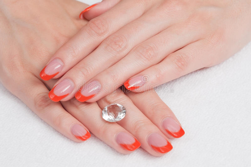 French manicure and diamond. Top view of woman hands with french manicure lying down and holding a gem stock photos
