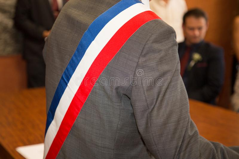 French mayor in grey suit with a scarf flag during a weeding day. A French mayor in grey suit with a scarf flag during a weeding day royalty free stock photography
