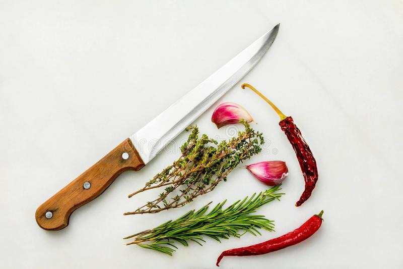 French Mediterranean cuisine ingredients herbs spices and condiments. Thyme rosemary garlic hot chili pepper kitchen knife marble. French Mediterranean cuisine stock photo