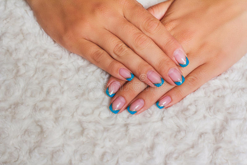 French nail art with light blue and gold lines stock photography