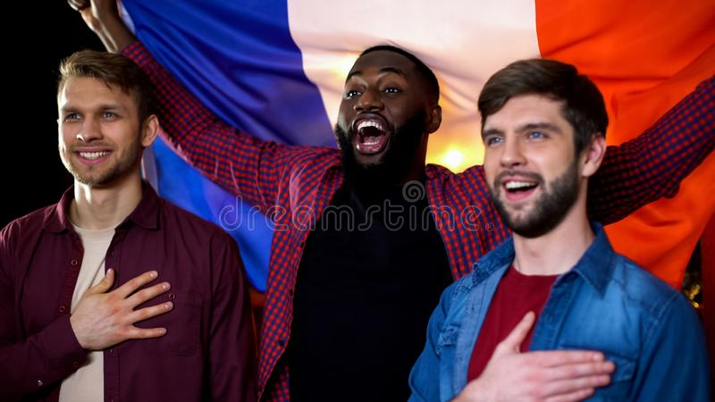 French national team supporters listening to anthem holding flag, patriotism. Stock photo royalty free stock photo