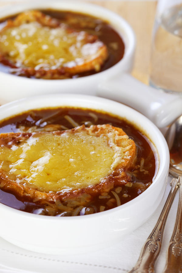 French Onion Soup. Famous French dish, French onion soup. Caramelised onions cooked in stock with wine and herbs, topped with toasted baguette and cheese and royalty free stock photos
