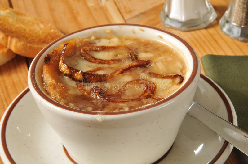 French onion soup. A cup of French Onion Soup on a rustic wooden table stock photo