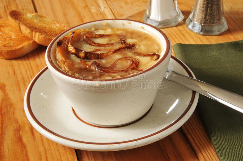 French onion soup. A cup of French Onion soup with toast and gruyere cheese royalty free stock photos