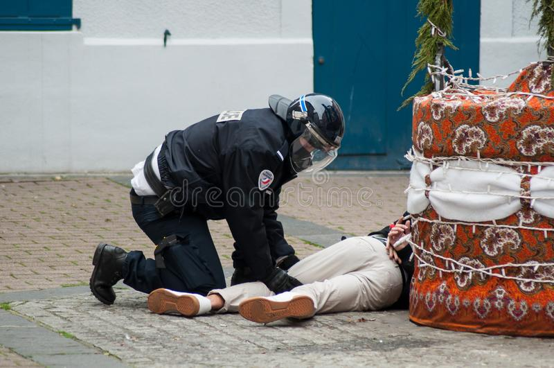 French policeman handcuffing a young man on the floor during riot of high school students on the sidelines of the movement of yell stock photos