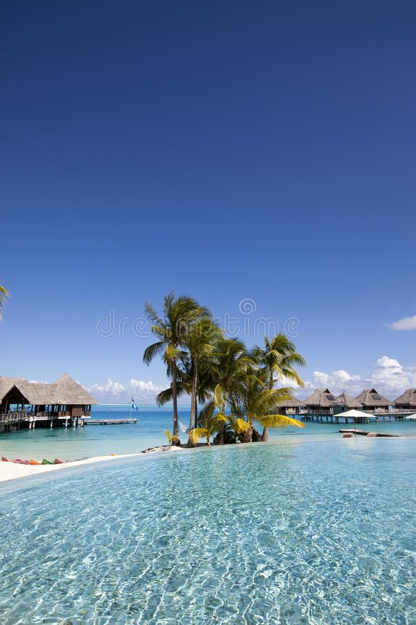 French Polynesia. Over water bungalows, sandy beach with palm trees and pool, Bora Bora.  stock photography