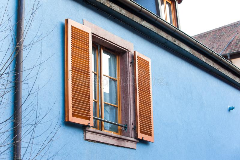 French provencal style blue house wall with windows. Alsace, Fra. Typical French provencal style vibrant blue colored house wall with windows and brown wooden royalty free stock photo
