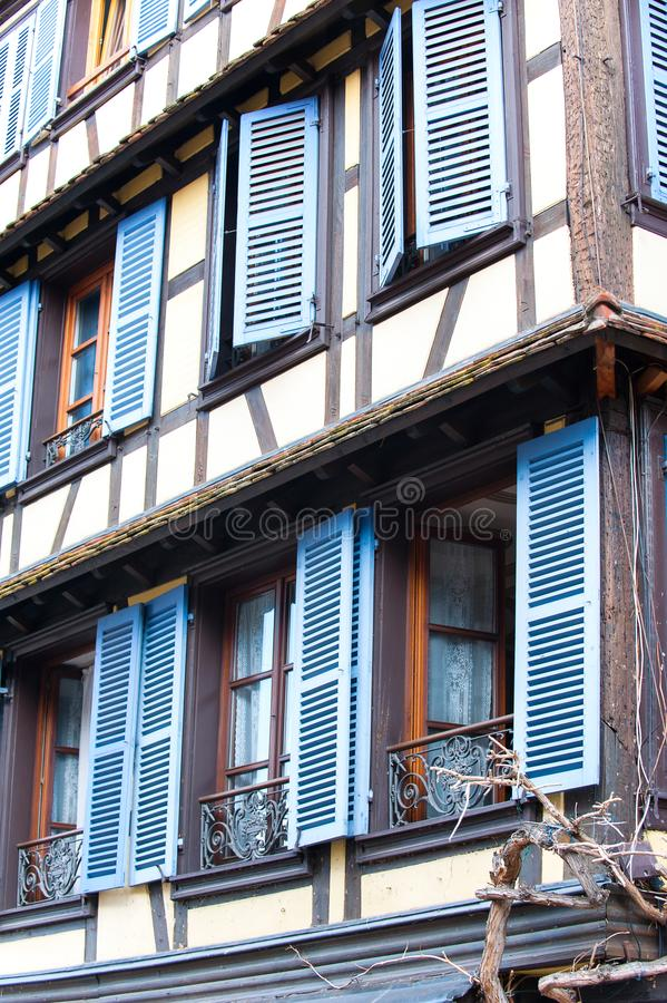 French provencal style windows with blue wooden shutters. Alsace. Typical French provencal style windows with vibrant blue wooden shutters and decorative iron stock image