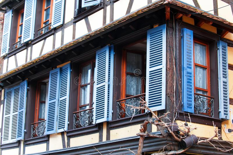 French provencal style windows with blue wooden shutters. Alsace. Typical French provencal style windows with vibrant blue wooden shutters and decorative iron stock photos