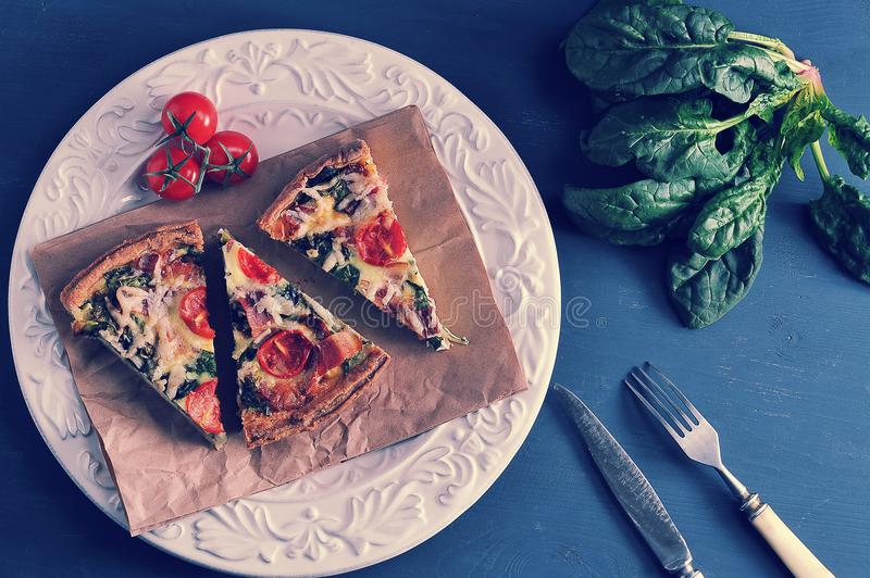 French quiche with eggs, spinach, tomatoes and bacon - the recipe for a delicious dish stock images