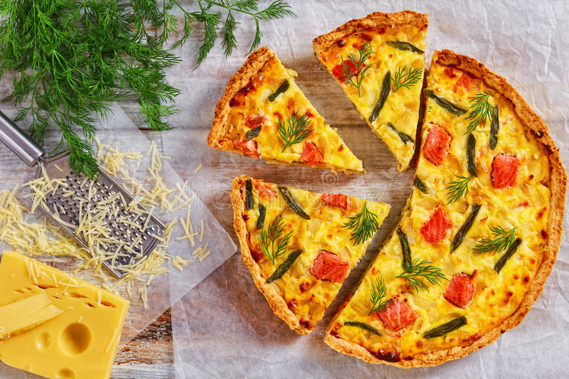 French quiche with Salmon, green bean and cheese. Delicious homemade french quiche with Salmon, green bean and Emmental cheese, cream, onion and eggs cut in royalty free stock photos