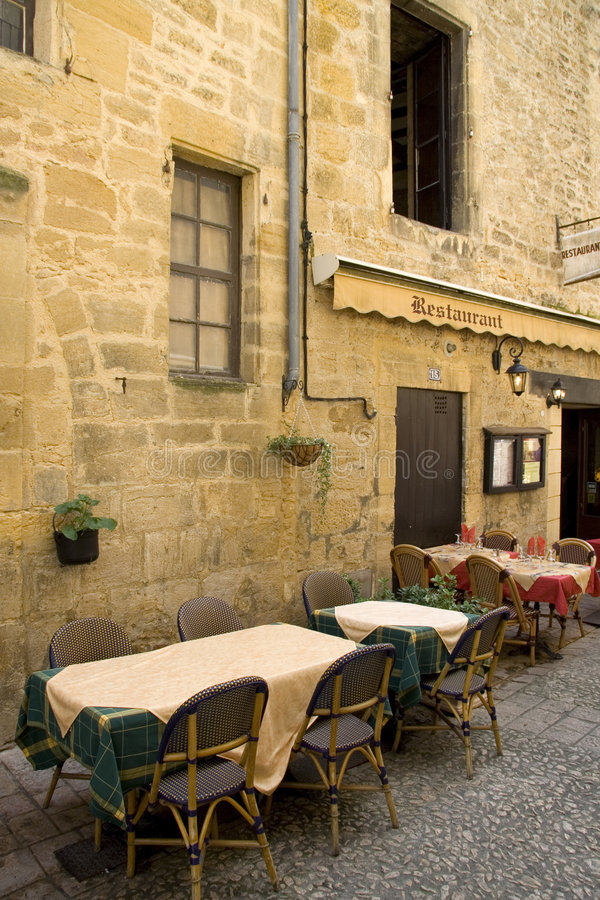 French restaurant. Tables set outside at a French restaurant on a small cobbled street stock image