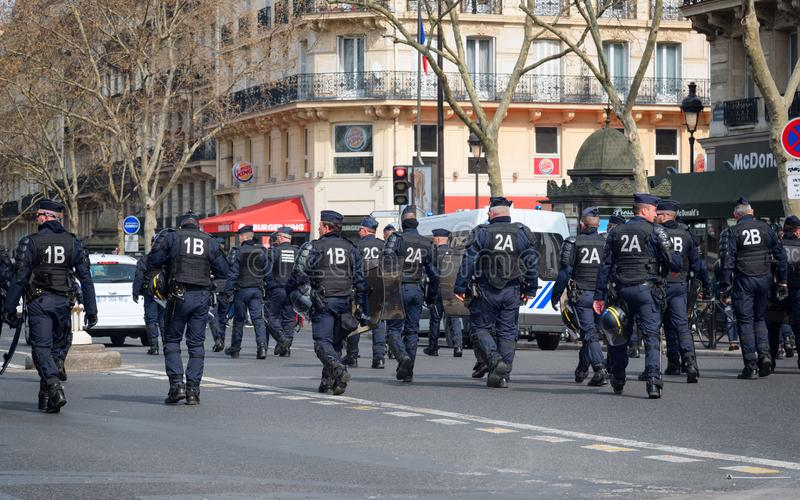 French riot police in the street during yellow vests Gilets jaunes protest in Paris. Paris, France - 22nd March, 2019: French policemen and armed forces marching stock image