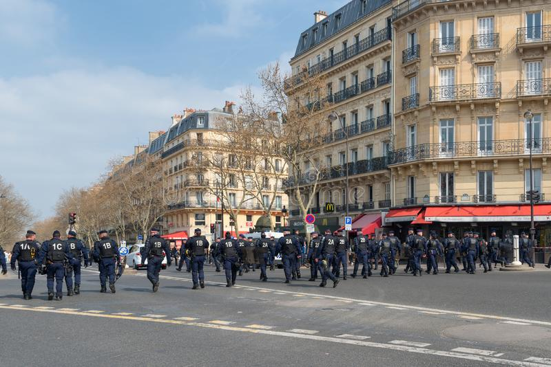 French riot police during yellow vests Gilets jaunes protest in Paris. Paris, France - 22nd March, 2019: French policemen and armed forces marching in the street royalty free stock images