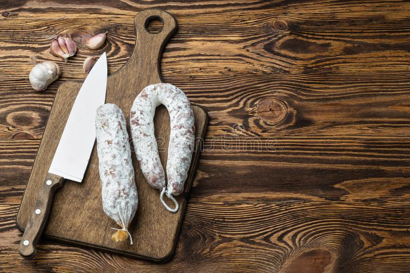 French salami on cutting board on wooden table stock photography