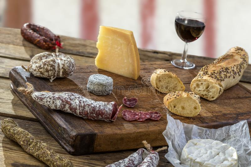 French Snacks with wine - various types of cheeses, bread , dry saussages, charcuterie, red vine on a gray background stock photo